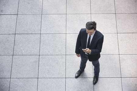 businessman phone: Elevated view of an Asian businessman using his Smart phone.