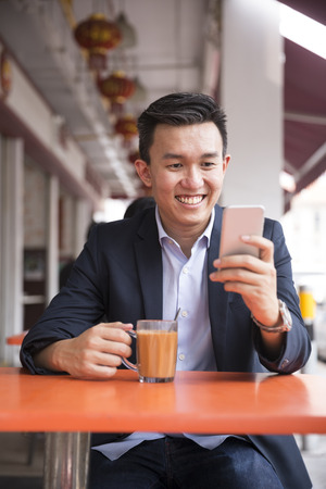 hawker: Chinese business man drinking a cup of coffee while sitting with his phone in an Asian food court or Hawker centre cafe.