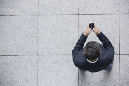handphone: Elevated view of an Asian businessman using his Smart phone.