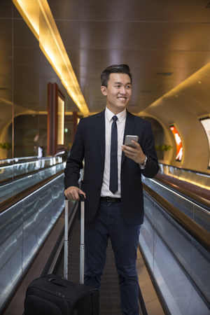 Chinese business Man using his Smart phone on a moving walkwaytravelator. Asian business traveller.