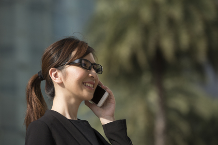 phone calls: Portrait of an Chinese businesswoman standing outside using her smart phone.
