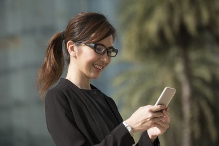 phone message: Portrait of an Chinese businesswoman standing outside using her smart phone.