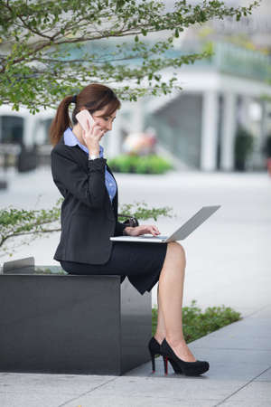 out of doors: Chinese business woman using his laptop out doors in modern city. Business on the move concept. Stock Photo