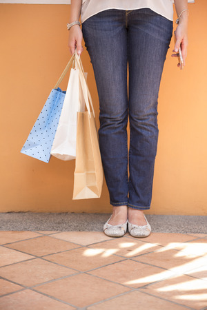 closeup on bags: Close up of shopping bags and a womans feet while standing on an urban street.