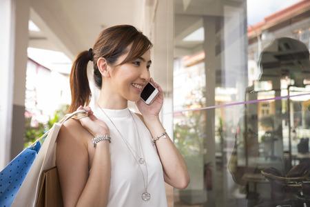 幸せな中国の女性のスマート フォンを使用し、買い物袋。