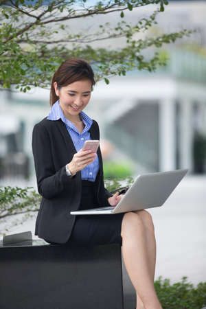 asian businesswoman: Chinese business woman using his laptop out doors in modern city. Business on the move concept. Stock Photo