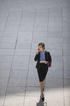 Above view of a happy Asian Businesswoman walking on city street using a smart phone.