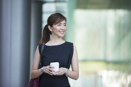 chinese lady: Asian business woman standing outside with office buildings in the background. Portrait of a Chinese business woman looking at the camera. Stock Photo