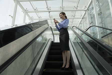 business technology: Chinese businesswoman using her Smart phone on an escalator.