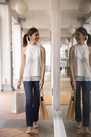 asian shopper: Happy Chinese woman walking on an urban street, holding shopping bags.