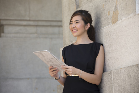 intelligent: Portrait of a happy Chinese business woman reading a newspaper outside an office building.