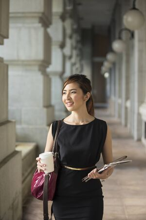 happy work: Asian business woman standing outside with office buildings in the background. Portrait of a Chinese business woman looking at the camera. Stock Photo