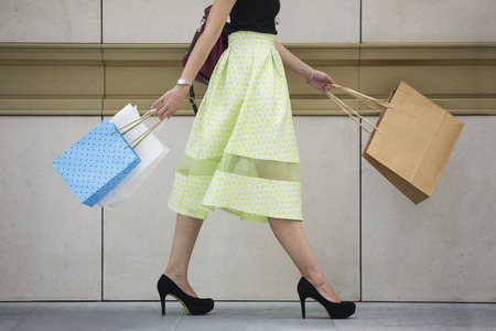 stilletto: Close up of an Asian woman holding shopping bags while walking on an urban street. Stock Photo