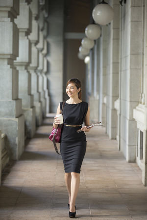 woman in office: Asian business woman standing outside with office buildings in the background. Portrait of a Chinese business woman looking at the camera. Stock Photo