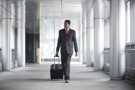 indian professional: Portrait of a confident Indian businessman walking in the city. Stock Photo