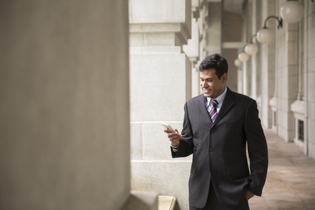 business man phone: Indian business Man using his Smart phone outdoors in Asian city.