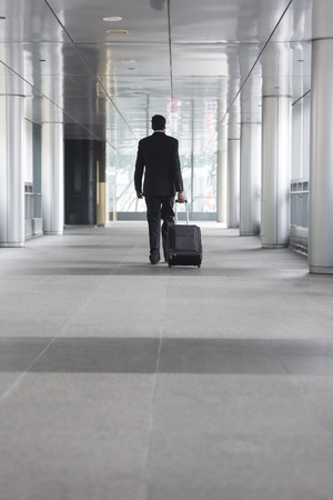 business traveller: Back view of an Indian businessman walking away from camera in the city. Stock Photo