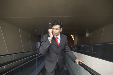 business man phone: Indian business Man using his Smart phone while standing on an escalator in the city.