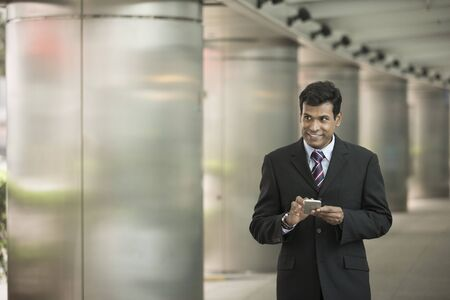 using phone: Indian business Man using his Smart phone outdoors in Asian city.