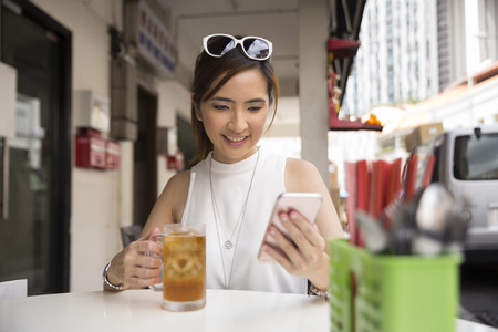 ice lemon tea: Chinese woman drinking an ice lemon tea, while sitting with her phone in an Asian food court or Hawker centre cafe.