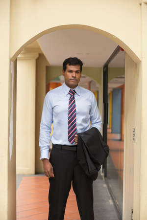 man looking: Indian business man in Asian city. Portrait of a serious Indian businessman looking at the camera. Stock Photo