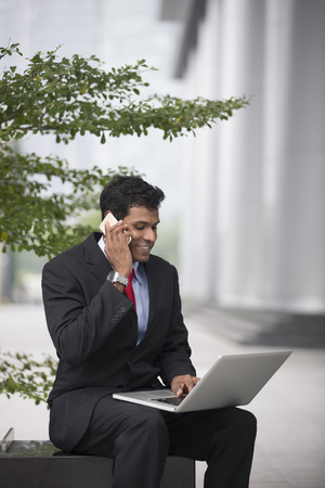 out of doors: Indian business Man using his laptop out doors in modern city. Business on the move concept.
