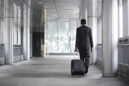 Achtermening van een Indische zakenman die vanaf camera in de stad lopen.