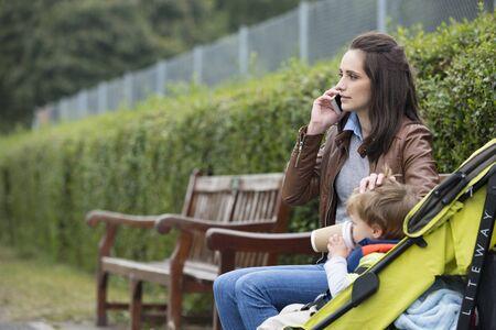 Madre ocupada que usa el teléfono móvil con el niño sentado en el cochecito. Foto de archivo