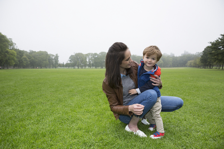 mother love: Portrait of a happy Mother holding son outdoors. Love and togetherness concept.