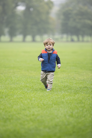niño corriendo: Portrait of a happy young boy running and playing outdoors. Foto de archivo