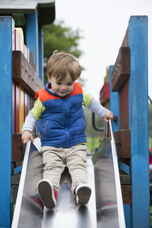 slide: Young Happy boy having fun at playground. Stock Photo
