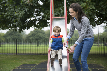 mom son: Happy Mum having fun with her boy at a playground. Love and togetherness concept.