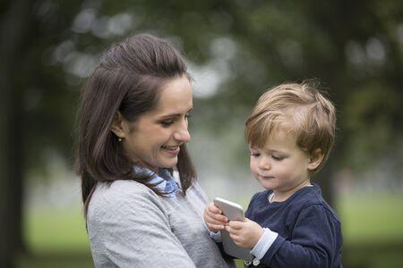 madre soltera: Niño jugando con sus madres teléfono inteligente. Foto de archivo