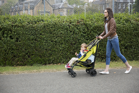 madre soltera: Side view of a Caucasian Mum walking on city street while pushing her toddler sitting in a pram.