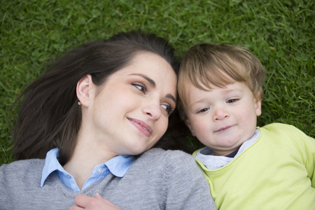 mother love: Portrait of a happy Mother and son lying on the grass. Love and togetherness concept. Stock Photo