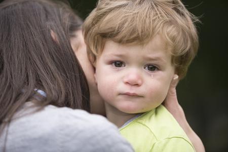 Droevige kleine jongen wordt door zijn moeder omhelsd. Ouderlijkheid, liefde en samenhorigheid concept.