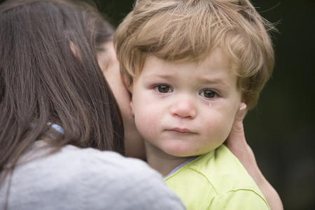 mother love: Sad little boy being hugged by his mother. Parenthood, Love and togetherness concept. Stock Photo