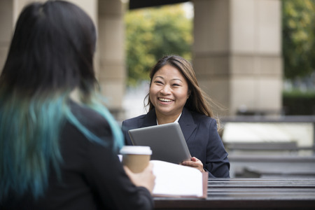 casual office: Two Asian Business women meeting in a cafe. Female Asian business colleagues sitting in a cafe.