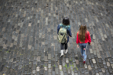 angle: High angle view of the back of two cool Asian women walking accross a road, one with a skateboard.