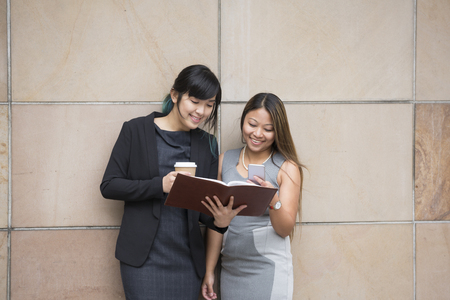 work together: Two Asian Business women using a Smartphone, outside there office building.