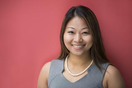 Porträt einer schönen Filipino Geschäftsfrau in Smart-Business-Anzug lehnt gegen eine rote Wand.