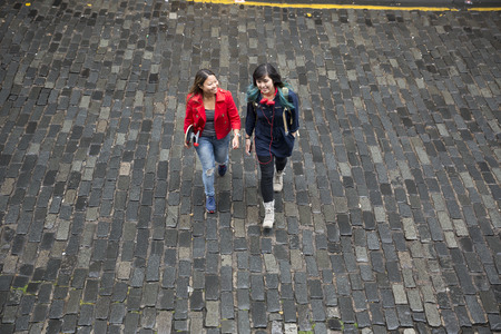 angle: A high angle view of two cool Asian women walking accross a road, one with a skateboard.