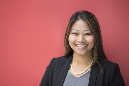 Portrait of a beautiful Filipino businesswoman in smart business suit leaning against a red wall. Standard-Bild