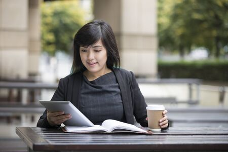 casual office: Chinese Businesswoman working in a cafe. Female Asian business woman sitting using a tablet PC in a cafe.