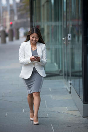 asian businesswoman: Portrait of an Asian businesswoman standing outside using her smart phone. Stock Photo