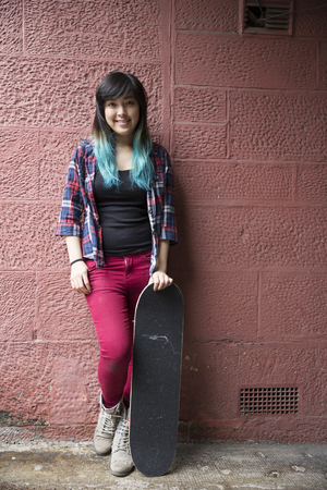 asia people: Portrait of a Young Asian woman holding skateboard and leaning against a wall. Stock Photo
