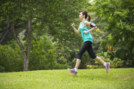 Athletic Asian woman running outdoors. Action and healthy lifestyle concept.