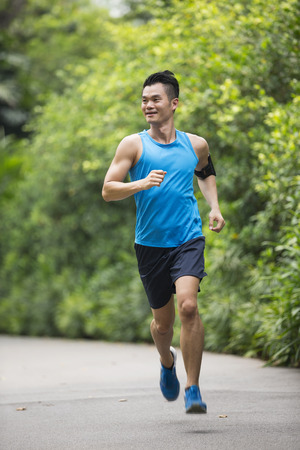Athletic Asian man running outdoors. Action and healthy lifestyle concept. Stock Photo