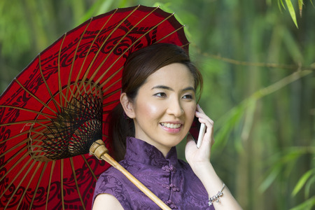 chinese dress: Chinese Woman talking on a Smart Phone and wearing a Cheongsam Chinese Dress with traditional umbrella.