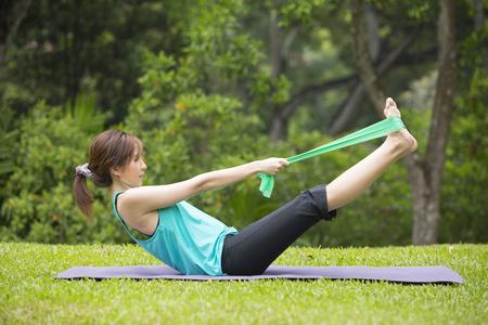 Athletic Asian woman exercising with a resistance band. Action and healthy lifestyle concept. Zdjęcie Seryjne